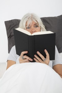 Close up of a Mid age woman reading book in bed, from high angle